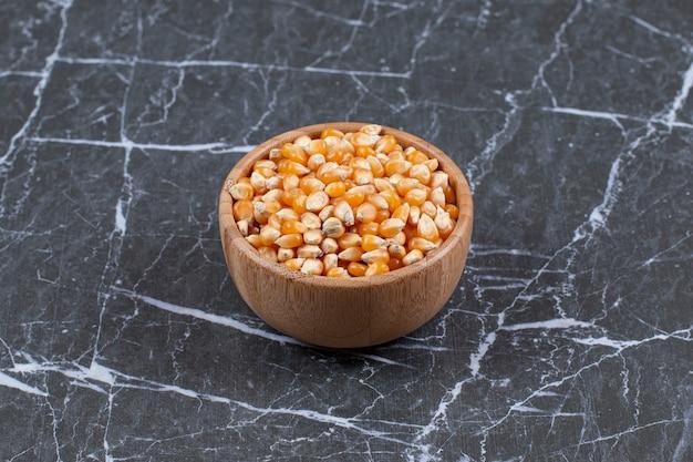 Feche a foto de uma tigela de madeira cheia de sementes de milho.
