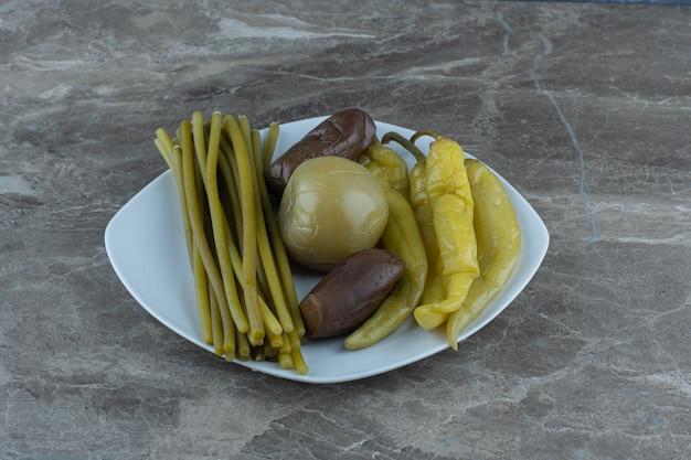 Feche a foto de vegetais enlatados no prato.