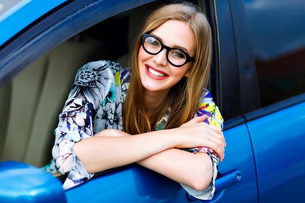 Feche a foto de viagens ao ar livre, estilo de vida, de mulher jovem loira hippie dirigindo carro, óculos e roupas brilhantes, grande sorriso, humor feliz, aproveite seu bom dia, jovem empresária.