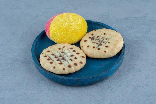 Feche a foto do biscoito caseiro na placa de madeira azul.