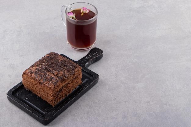 Feche a foto do bolo de chocolate na placa de madeira e uma xícara de chá sobre um fundo cinza.