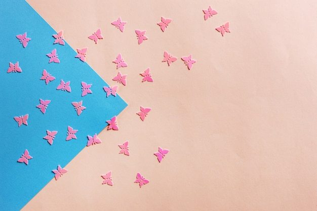 Feche a foto do brilho da borboleta rosa confetty no fundo colorido rosa e azul. vista superior, primavera, conceito de páscoa