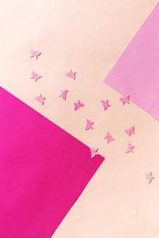 Feche a foto do brilho da borboleta rosa confetty no fundo rosa colorido. vista superior, primavera, páscoa e vários conceitos de feriados e eventos