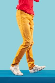 Feche a foto do cara charmoso com roupa colorida em fundo brilhante do estúdio. moda, humor, estilo, conceito de roupas. cultura jovem, copyspace. para vendas ou publicidade