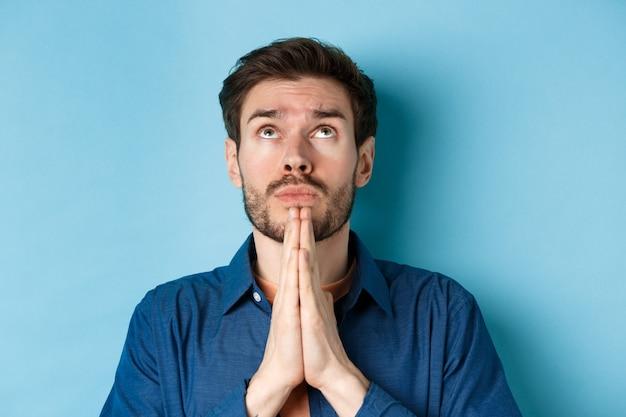 Feche a foto do cara esperançoso suplicando a deus, de mãos dadas em gesto de imploração e olhando para o céu, de pé sobre fundo azul suplicando.