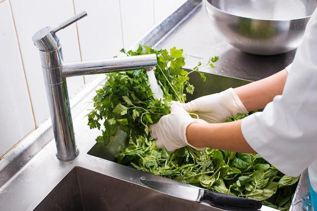 Feche a foto do chef lavando salsa na cozinha