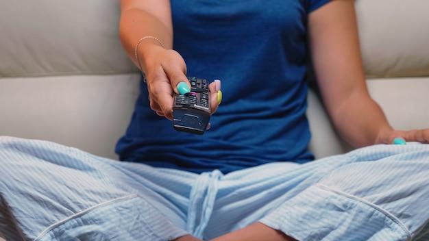Feche a foto do controlador na mão de uma mulher enquanto está sentado no sofá. controle remoto nas mãos da pessoa que aponta para a tv, pressionando o botão e mudando os canais sentado em frente à televisão.