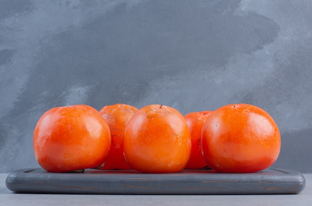Feche a foto do fruto do caqui laranja maduro. na placa de madeira.
