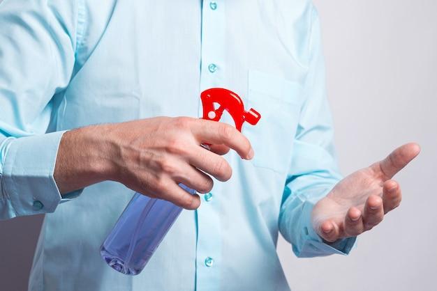 Feche a foto do homem borrifando as mãos com desinfetante para as mãos durante o período de pandemia.