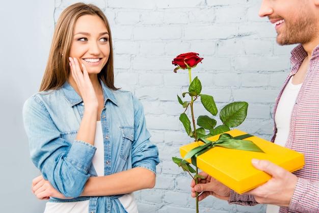 Feche a foto do homem dando um presente e rosa para a namorada