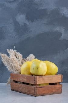 Feche a foto do marmelo de maçã na cesta de madeira.