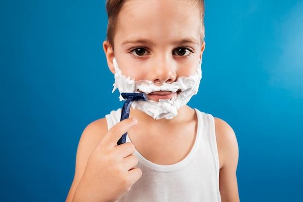 Feche a foto do menino sorridente, tentando barbear o rosto