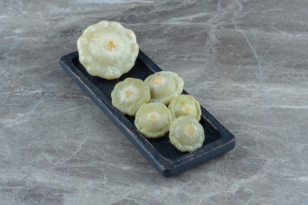 Feche a foto do pickle verde patty pan squash na placa preta.