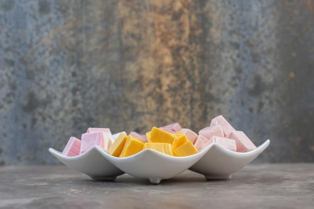 Feche a foto do prato branco cheio de doces coloridos.