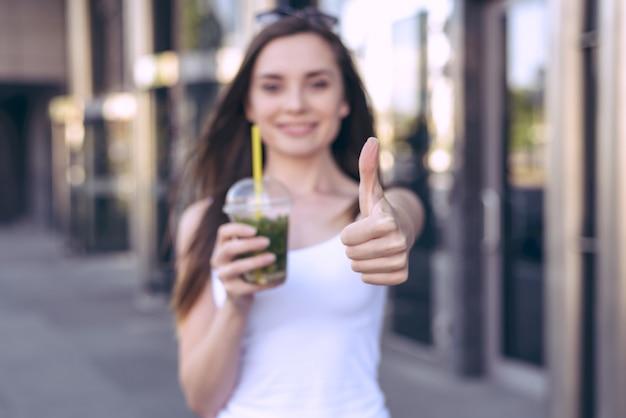 Feche a foto do retrato de uma pessoa bonita mostrando o polegar para cima, ok, negócio feito gesto