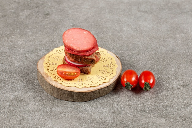Feche a foto do sanduíche caseiro com tomate na placa de madeira.