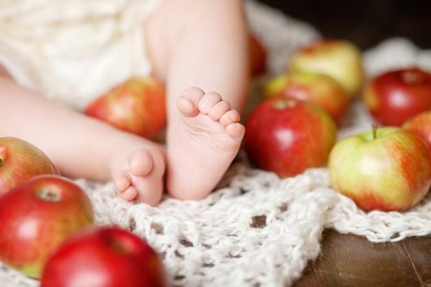 Feche a foto dos pés do bebê recém-nascido em uma manta de malha e maçãs