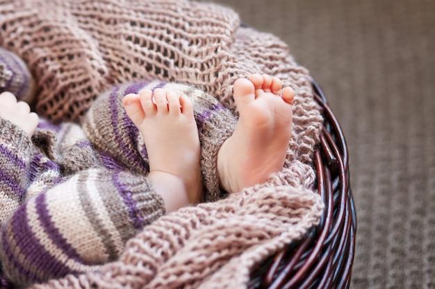 Feche a foto dos pés do bebê recém-nascido em uma manta de malha em uma cesta de papelão