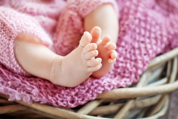 Feche a foto dos pés do bebê recém-nascido em uma manta de malha