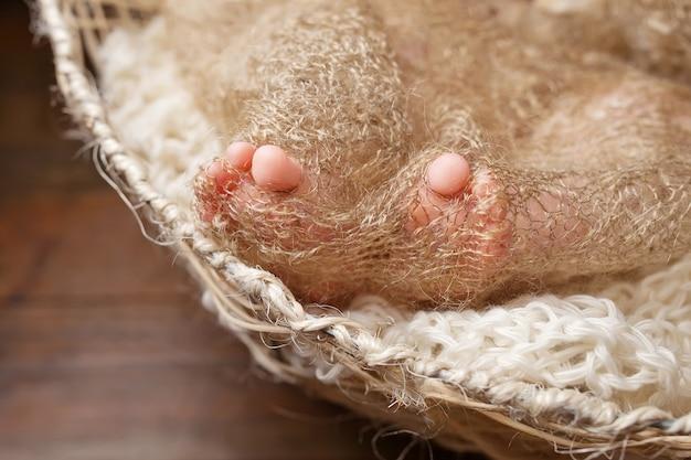 Feche a foto dos pés do bebê recém-nascido na manta de malha em uma cesta aeparada.