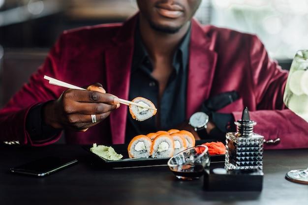 Feche a foto. homem africano, americano, comendo sushi no restaurante.