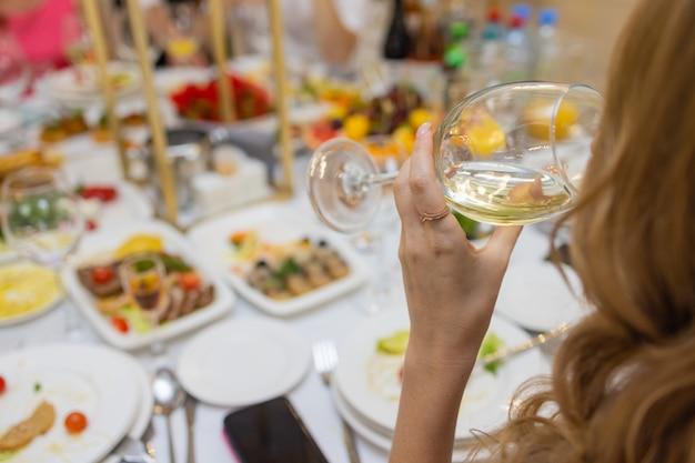 Feche a foto recortada da mesa durante o jantar romântico com as mãos do amante com copos de vinho e comida.