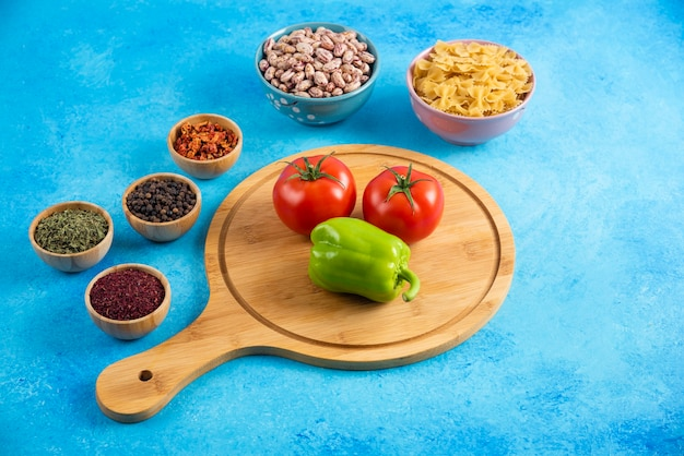 Feche a foto. tomate e pimenta na placa de madeira na frente de duas tigelas. feijão e macarrão.