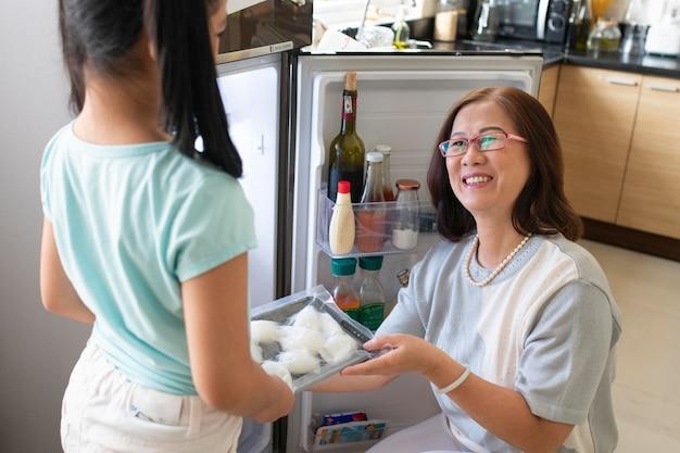 Feche a garota e a mulher na cozinha