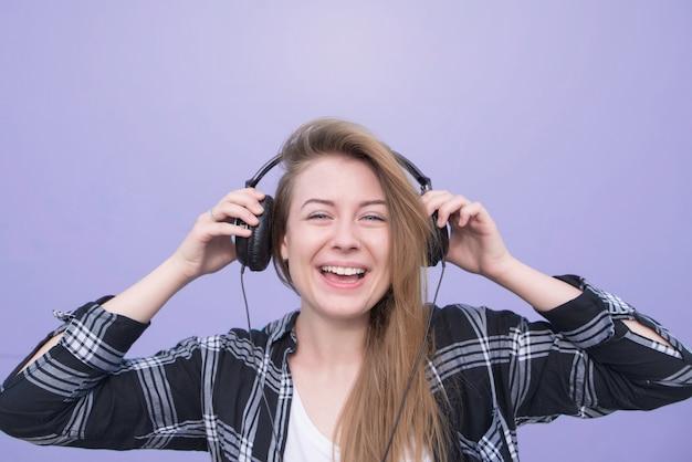 Feche a garota feliz retrato que ouve música em fones de ouvido em um fundo roxo, olha para a câmera e sorri. jovem mulher ouve música nos fones de ouvido isolados em um fundo roxo