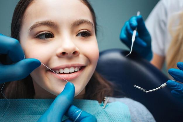 Feche a garota na cadeira odontológica. mão para fio dental dentes da frente. as mãos de mulher segurar ferramentas.