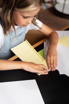 Feche a garota sendo criativa com o papel