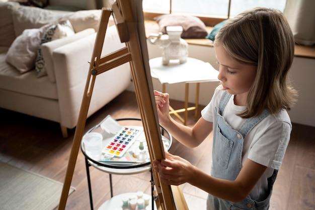 Feche a garota sendo criativa em casa