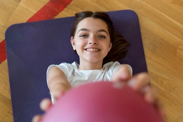 Feche a garota sorridente com a bola