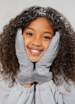 Feche a garota sorridente com neve