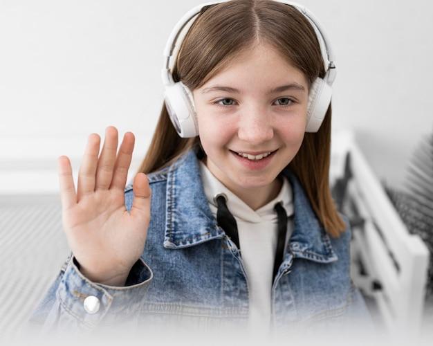 Feche a garota sorridente usando fones de ouvido