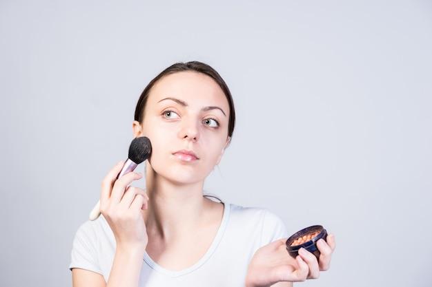 Feche a garota vaidosa aplicando maquiagem base no rosto usando o pincel enquanto olha para o canto superior esquerdo da moldura em um fundo cinza.