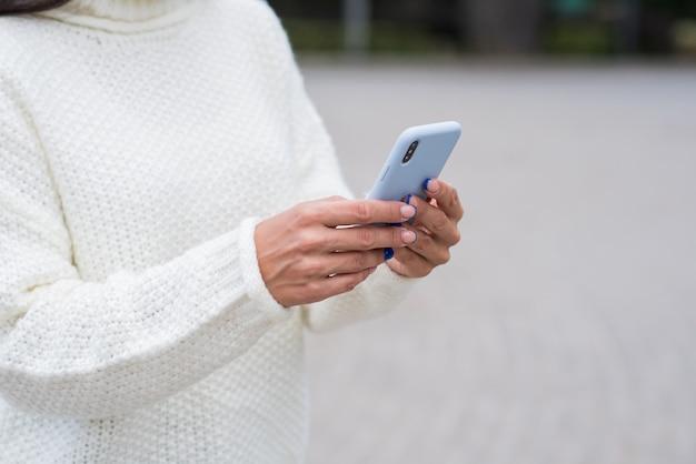 Feche a imagem com as mãos femininas usando um smartphone.