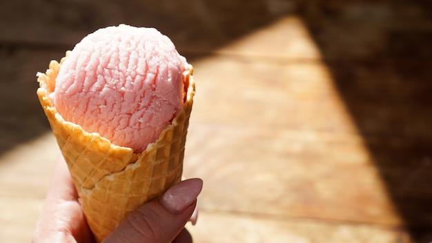 Feche a imagem da mão de uma mulher segurando dois cones de waffle frescos com sorvete de framboesa no fundo de madeira