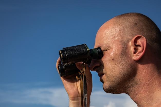 Feche a imagem da mão do homem careca segurando ou olhando, assistindo usando binóculos no céu azul nublado.
