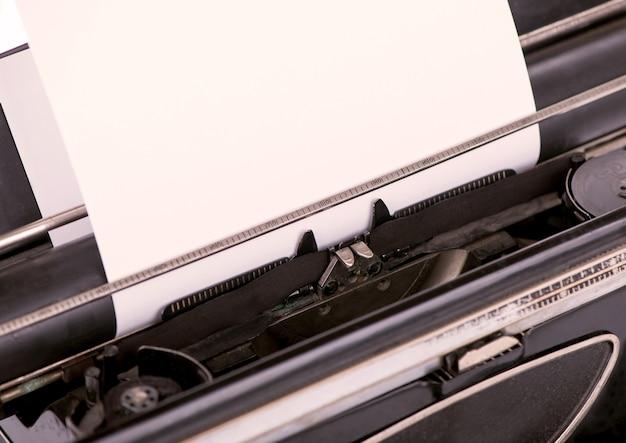 Feche a imagem da máquina de escrever com a folha de papel.