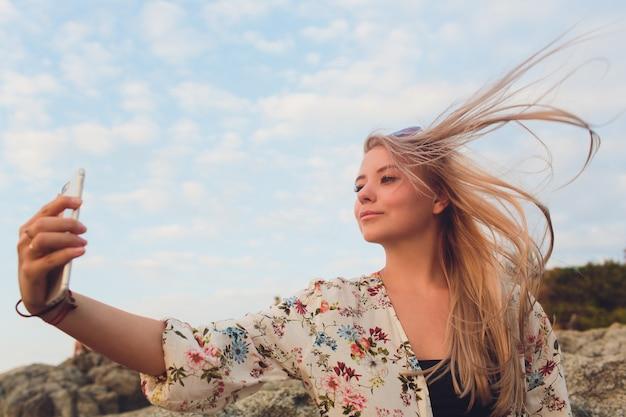 Feche a imagem da mulher loira feliz fazendo selfie na praia.