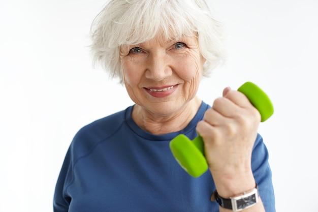 Feche a imagem da mulher madura desportiva enérgica com cabelos grisalhos e rugas, exercitando-se dentro de casa, fazendo bíceps, segurando halteres verdes e sorrindo alegremente. esportes, idade e condicionamento físico