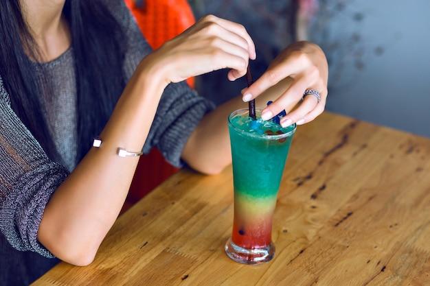Feche a imagem da mulher segurando saboroso arco-íris colorido saboroso álcool doce coquetel, hora da festa de verão.