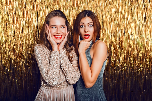 Feche a imagem de estúdio de duas incríveis garotas comemorando sensuais com lábios vermelhos, rosto de surpresa