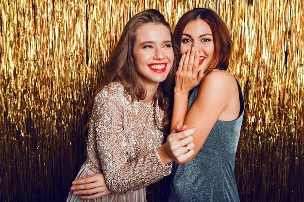 Feche a imagem de estúdio de duas incríveis garotas comemorando sensuais com lábios vermelhos,