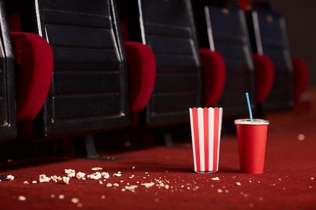 Feche a imagem de fundo do copo de refrigerante e da pipoca no chão vermelho bagunçado de um cinema vazio, copie o espaço