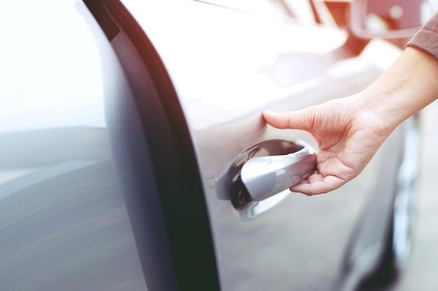 Feche a imagem de um empresário com a mão na alça abrindo a porta de um carro.