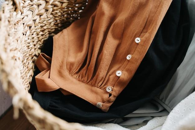 Feche a imagem de uma cesta de vime cheia de vestidos de verão para lavar a roupa. vista do topo.