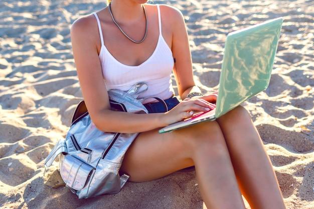Feche a imagem de uma jovem sentada na praia e trabalhando em seu laptop, mochila, estilo freelance. trabalho nas férias.