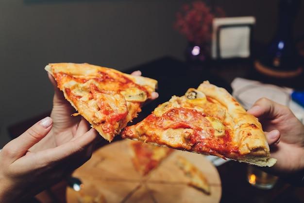 Feche a imagem de uma mulher com as mãos segurando uma fatia de pizza.